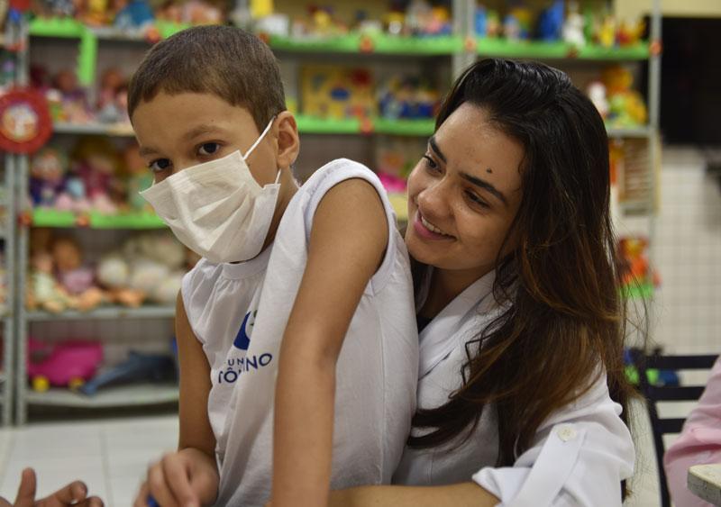 Colaboradora com paciente infantil no colo
